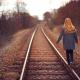 Rear view of a girl walking along railway lines