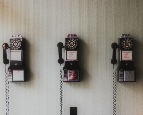Three historic phones hanging on the wall.