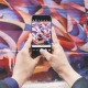 A pair of hands holding a mobile phone, taking a photograph of colourful graffiti